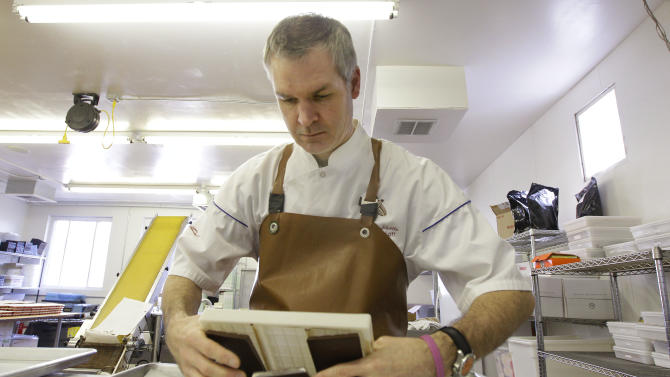 """Andrew Shotts owner of Garrison Confections, removes dark chocolate bars from their molds while making his candy for the """"Save Chocolateville"""" fundraising campaign in Central Falls , RI., a city  struggles through bankruptcy, Thursday afternoon, Feb. 23, 2012. Central Falls was once the home of a thriving chocolate manufacturer known as Chocolateville for the 18th century chocolate mill located there. (AP Photo/Stephan Savoia)"""