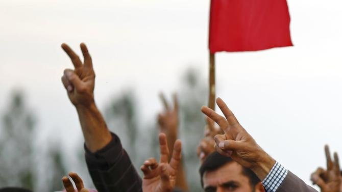 Turkish Kurds show victory sign during the funeral of Kurdish fighters killed during clashes against Islamic State in Syrian town of Kobani, at a cemetery in the southeastern town of Suruc