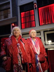 Decked out in matching red leather jackets and boots, red jeans and crocheted red berets, with Stars and Stripes scarves draped around their necks, the Fokkens cut a jaunty pair as they saunter down alleys with red-framed windows where semi-nude 'working women' put their bodies on display to lure customers