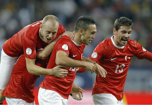 Turkey's Mevlut Erdinc, center, celebrates scoring his team's second goal during a World Cup Group D qualifying soccer match against Romania at the National Arena stadium in Bucharest, Romania, Tuesda