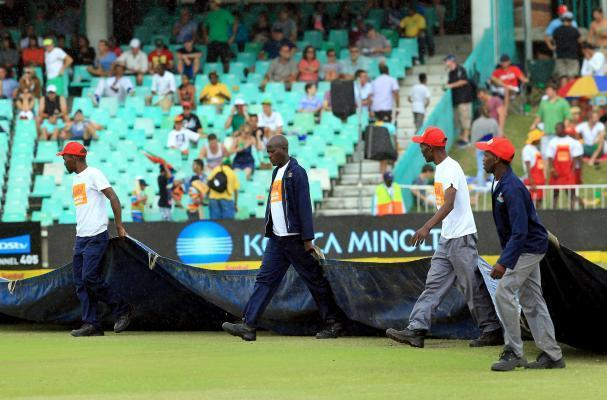 Ground staff cover the ground as it bigins to rain during the 4th Day of the Second Test match between India and South Africa played at Kingsmead stadium in Durban on Dec.29, 2013. (Photo: IANS)