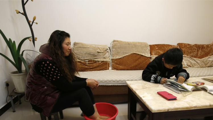 Liu Fei soaks her feet in a tub of water for a foot bath as she looks at her son Xiaojie doing his homework at their rented house in Beijing
