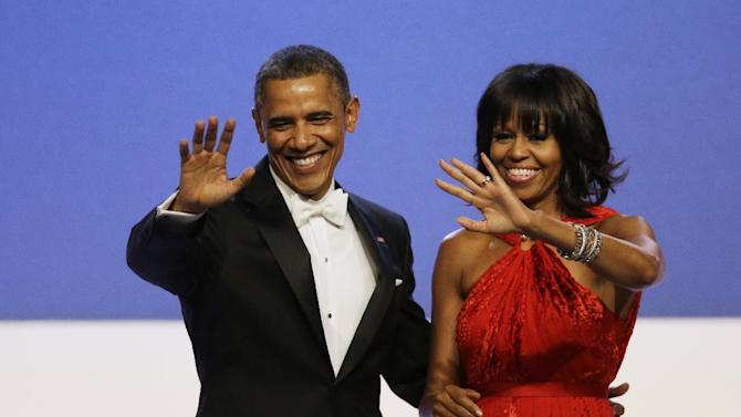 """FILE - In this Jan. 21, 2013, file photo, President Barack Obama and Michelle Obama wave to guests after their dance at the Inaugural Ball at the 57th Presidential Inauguration in Washington. Michelle Obama has a new look, both in person and online, and with the president's re-election, she has four more years as first lady, too. The first lady is trying to figure out what comes next for this self-described """"mom in chief"""" who also is a champion of healthier eating, an advocate for military families, a fitness buff and the best-selling author of a book about her White House garden. For certain, she'll press ahead with her well-publicized efforts to reduce childhood obesity and rally the country around its service members. (AP Photo/Paul Sancya, File)"""