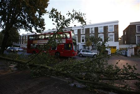 A bus travels past fallen trees in Islington, north London, after the St. Jude storm swept through southern parts of Britain