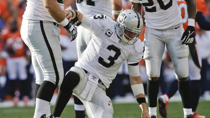 Oakland Raiders quarterback Carson Palmer (3) is helped up off the turf after taking a hit by the Denver Broncos during the fourth quarter of an NFL football game, Sunday, Sept. 30, 2012, in Denver. The Broncos won 37-6. (AP Photo/Joe Mahoney)