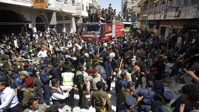 Yemeni security forces gather at the site of a plane crash in Sanaa, Yemen, Tuesday, Feb. 19, 2013. A Yemeni official says a military plane on a training exercise crashed into a neighborhood in the country's capital, Sanaa, killing and injuring scores of people. (AP Photo/Hani Mohammed)