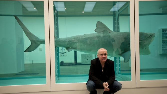 """British artist Damien Hirst beside the 1991 piece """"The Physical Impossibility of Death in the Mind of Someone Living"""", a tiger shark preserved in formaldehyde in a vitrine, during a media preview of the first substantial survey show of his work in the UK at the Tate Modern gallery in London, Monday, April 2, 2012.  The exhibition, timed for the culmination of the Cultural Olympiad and due to open to the public on Wednesday, showcases over 70 of Hirst's works since he first came to public attention in 1988.  (AP Photo/Matt Dunham)"""