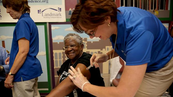 Kimberly Delp gives a flu shot to Carleen Matthews, of Pittsburgh, at the Flu + You Pittsburgh Event, at the Homewood Senior Center on Tuesday, Sept. 18, 2012 in Pittsburgh, Pa. The Flu + You initiative led by the Allegheny County Department of Human Services, Area Agency on Aging, and Northern Area Multi-Service Center aims to educate older adults about the dangers of flu, the importance of annual vaccination, and available vaccination options.  (Andrew Rush /AP Images for NCOA)