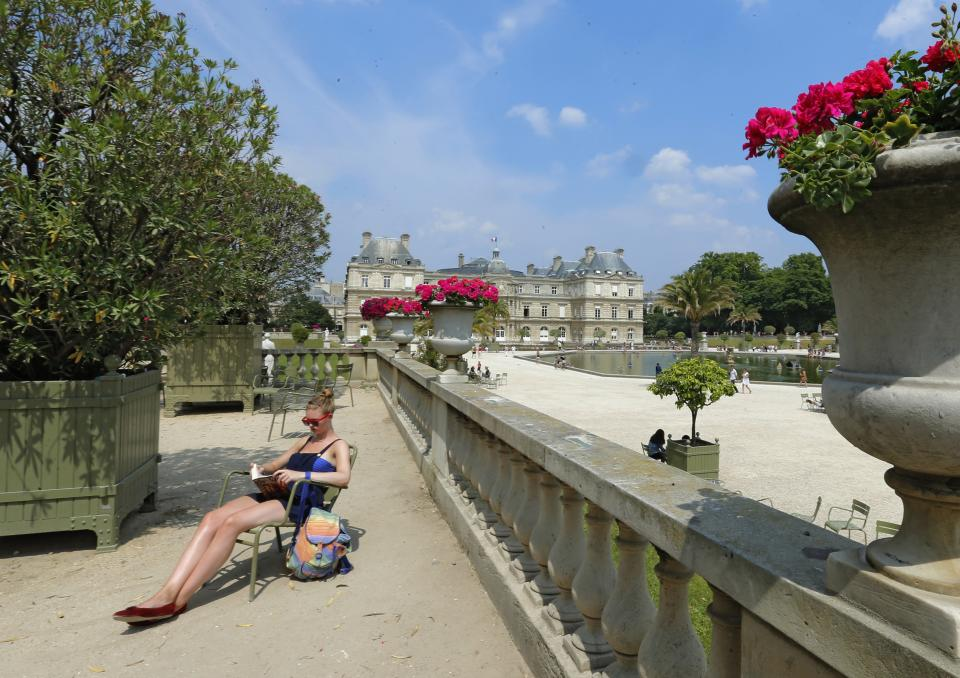 A women sunbathes in the Luxembourg gardens, Wednesday, July 17, 2013. The Luxembourg and Tuileries gardens are Paris' most famous, but the city is also edged by two woods: Vincennes in the east and Boulogne in the west. (AP Photo/Jacques Brinon)