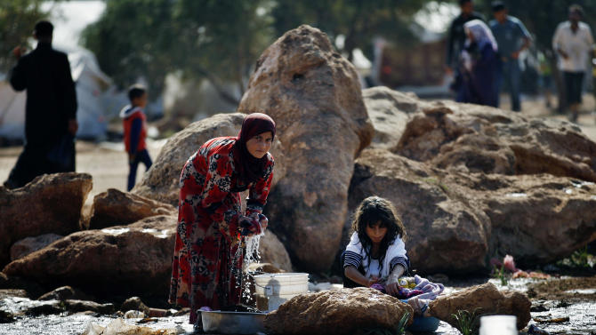 Syrian girls who fled from the violence in their village, wash their clothes at a displaced camp, in the Syrian village of Atma, near the Turkish border with Syria, Monday, Nov. 5, 2012. (AP Photo/ Khalil Hamra)