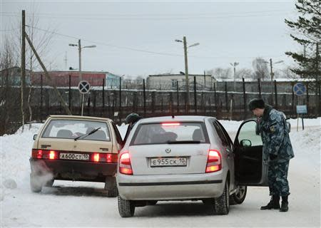 Police officers check cars on the road in front of the Penal Colony 7, where Mikhail Khodorkovsky was held at, in Segezha near the Finnish border