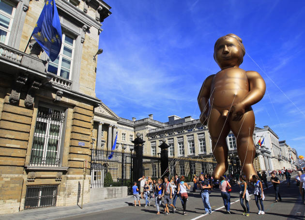 A giant balloon of Brussels' famous Manneken Pis statue floats past Belgian Parliament during the Balloon Day Parade in central Brussels