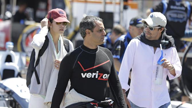 Juan Pablo Montoya, of Colombia, walks through the pit area to his car before practice for the IndyCar auto race Saturday, Aug. 23, 2014, in Sonoma, Calif