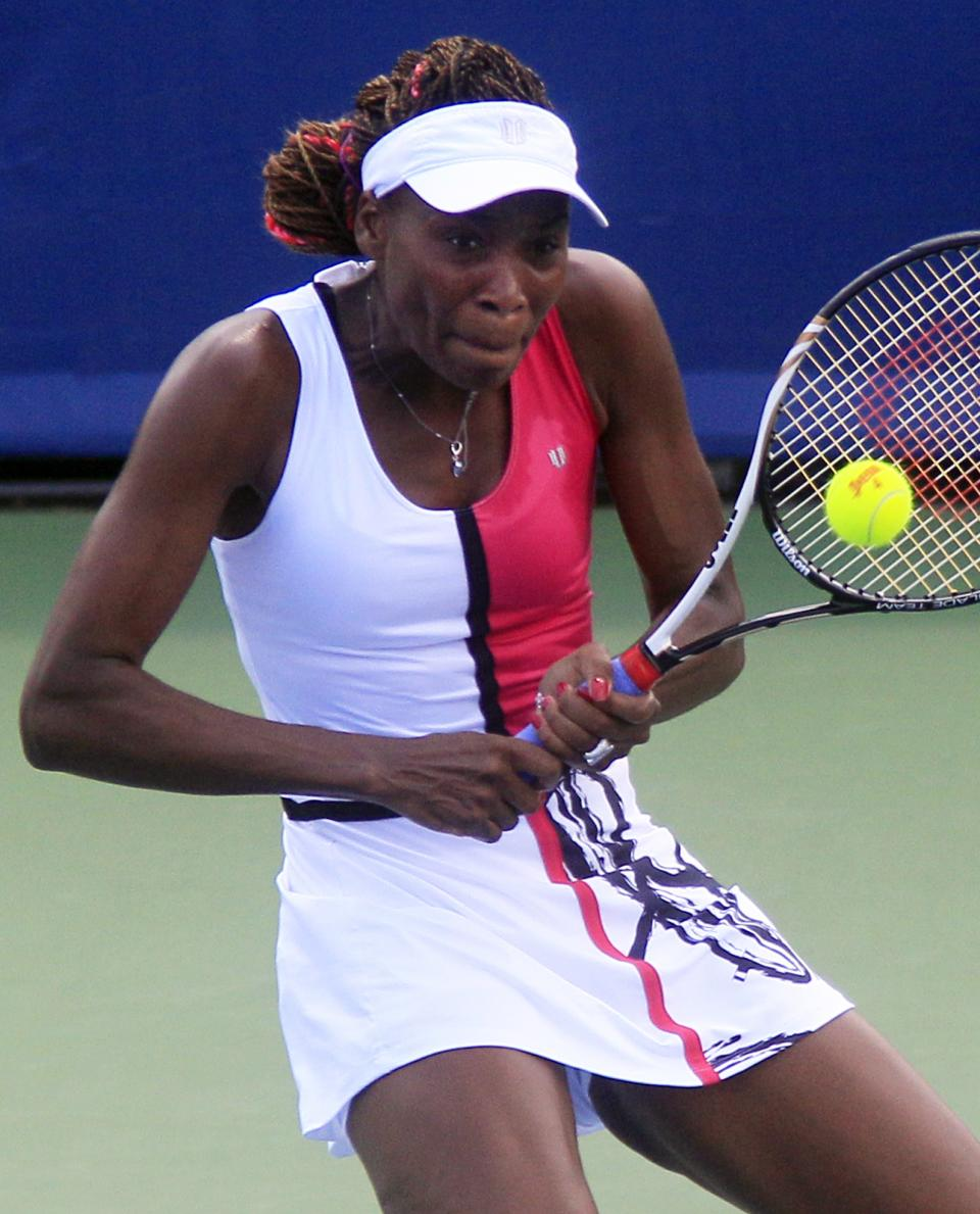Venus Williams returns a serve against Samantha Stosur, from Australia, during a quarterfinals match at the Western & Southern Open tennis tournament, Friday, Aug. 17, 2012, in Mason, Ohio. (AP Photo/Al Behrman)