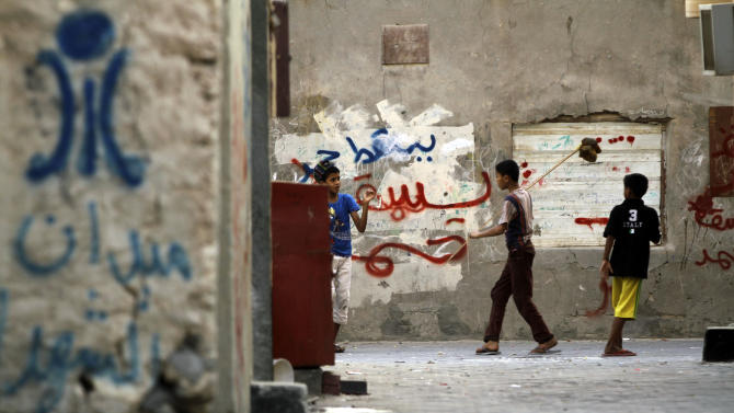 """Bahraini children play in an alley spray-painted with anti-government graffiti in Malkiya, Bahrain, on Monday, Aug. 6, 2012. At left above the words """"Martyrs Square,""""  is a painted image of the since-demolished monument that stood at the site of huge Spring 2011 pro-democracy protests. Back wall graffiti includes """"down Hamad,"""" referring to Bahrain's king. (AP Photo/Hasan Jamali)"""