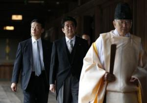 File photo of Japan's PM Abe being led by a Shinto priest as he visits Yasukuni shrine in Tokyo