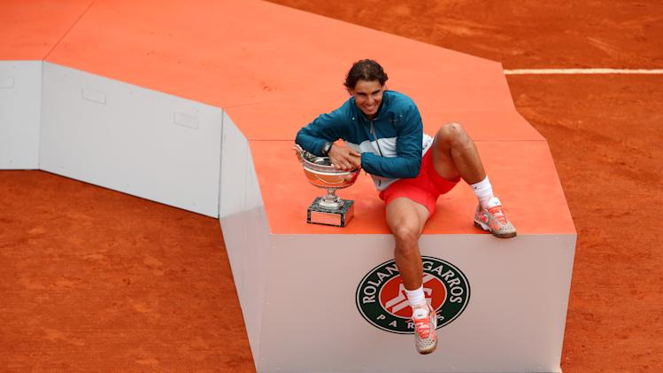 PARIS, FRANCE - JUNE 09:  Rafael Nadal of Spain celebrates victory with the Coupe des Mousquetaires trophy in the men's singles final against David Ferrer of Spain during day fifteen of the French Open at Roland Garros on June 9, 2013 in Paris, France.  (Photo by Julian Finney/Getty Images)