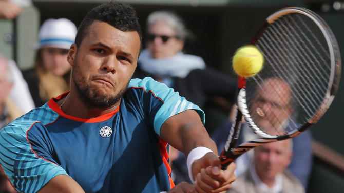 Jo-Wilfried Tsonga of France returns in his fourth round match against Stanislas Wawrinka of Switzerland at the French Open tennis tournament in Roland Garros stadium in Paris, Sunday June 3, 2012. (AP Photo/Michel Euler)