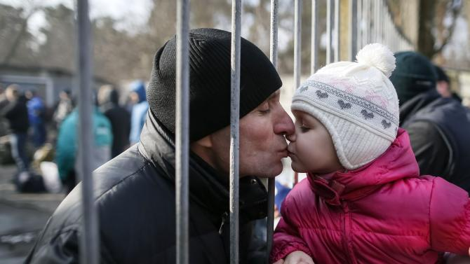 A girl kisses her father, a conscript, after a ceremony marking enrolment for new conscripts in the Ukrainian army in Kiev