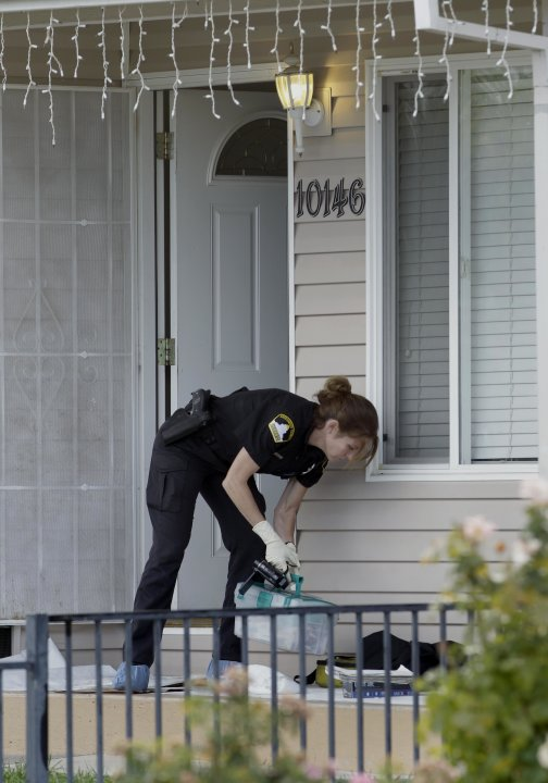 A Sacramento County Sheriffs Deputy  processes the murder scene, Wednesday, Oct. 24, 2012, where a mother and her two young children were found murdered in Rancho Cordova, Calif. The woman and her 2-y