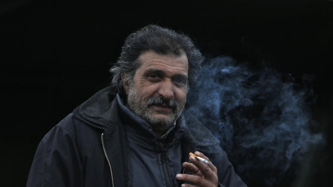 A migrant smokes a cigarette as migrants and refugees are registered by the authorities before continuing their train journey to western Europe at a refugee transit camp in Slavonski Brod