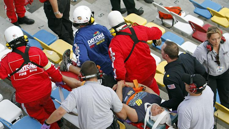 An injured spectator is treated after a crash at the conclusion of the NASCAR Nationwide Series auto race Saturday, Feb. 23, 2013, at Daytona International Speedway in Daytona Beach, Fla. Driver Kyle Larson's car hit the safety fence sending car parts and other debris flying into the stands. (AP Photo/David Graham)