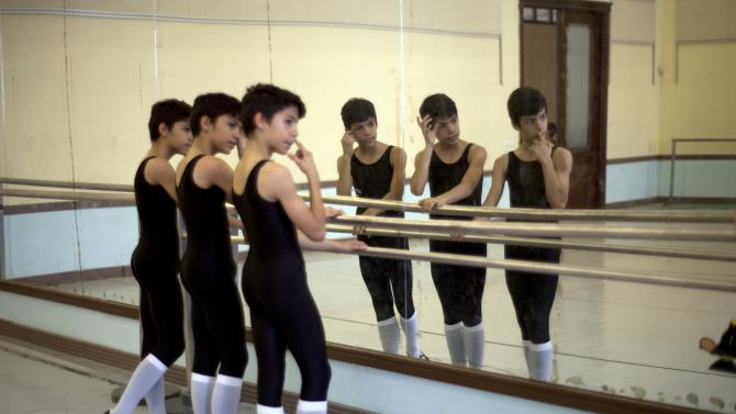 "In this April 3, 2013 photo, identical triplets Marcos, Cesar and Angel Ramirez Castellanos stand at the bar at the start of ballet class at the National School of Ballet in Havana, Cuba. The triplets say they fell in love with dance in 2007 when their mother took them to see a performance of ""The Nutcracker,"" which is put on every Christmas season and costs just pennies to attend. (AP Photo/Ramon Espinosa)"