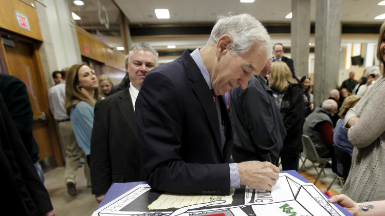 Republican presidential candidate Rep. Ron Paul, R-Texas, autographs a poster at a caucus site at Shawnee Mission Northwest High School  Saturday, March 10, 2012, in Shawnee, Kan. (AP Photo/Charlie Riedel)