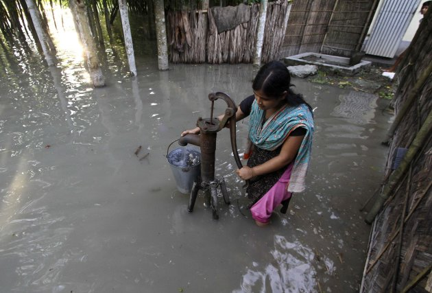 A flood-affected girl uses a submerged hand-pump at Dhuhibala village