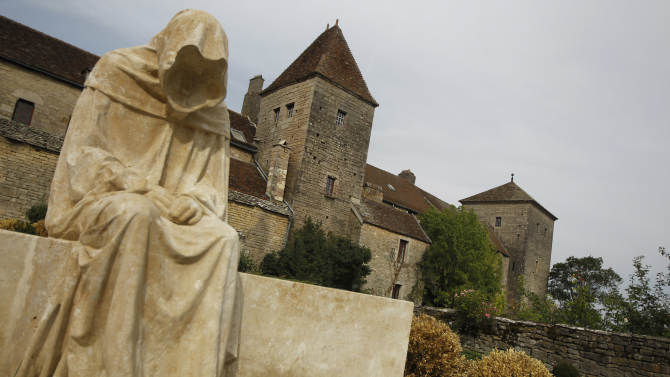 In this Sept. 10, 2012 photo, a modern sculpture of a monk by a French artist sits near the Gevrey-Chambertin castle in Burgundy, Eastern France. Gevrey-Chambertin is the kind of French village where the waiter chastises diners who don't order a glass of locally made wine, even at a midweek lunch. So when Louis Ng Chi Sing, a Macau casino magnate, purchased the thousand-year-old Chateau de Gevrey-Chambertin and some surrounding vineyards in May for 8 million euros ($10.5 million) it set off a firestorm. (AP Photo/Laurent Cipriani)