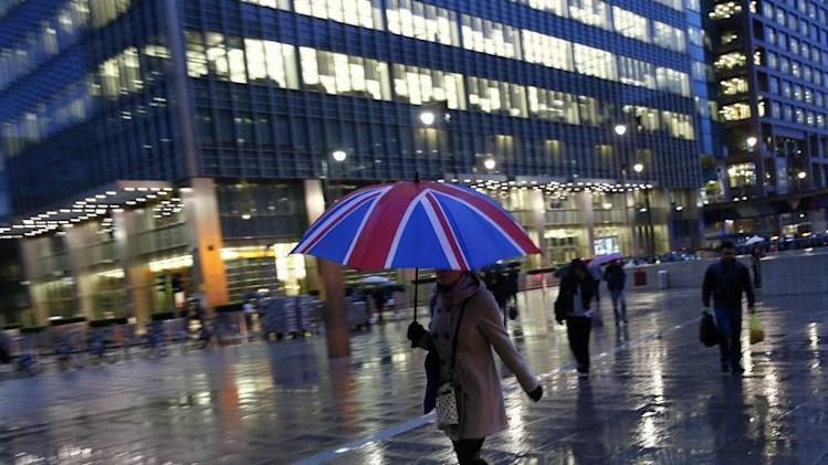 Workers walk in the rain at the Canary Wharf business district in London