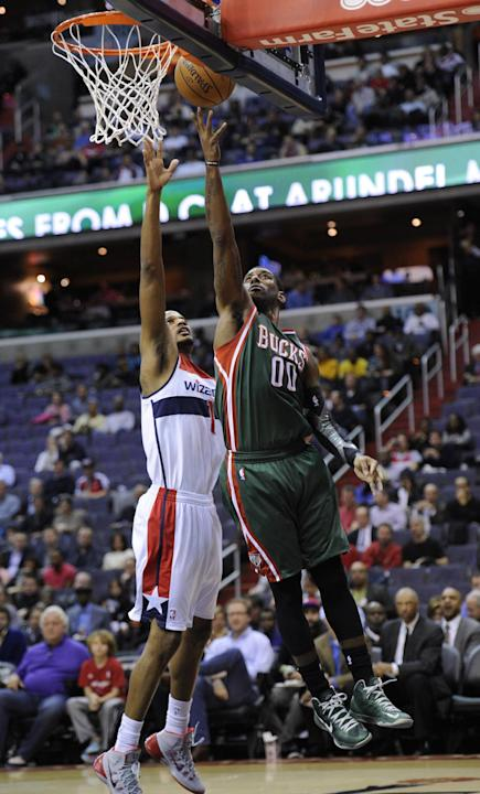 Milwaukee Bucks guard O.J. Mayo (00) goes to the basket against Washington Wizards forward Trevor Ariza (1) during the first half of an NBA basketball game on Friday, Dec. 6, 2013, in Washington. The