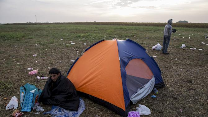 A migrant sits in front of his tent on a fielf near the village of Roszke, Hungary
