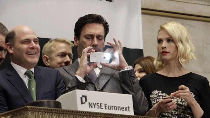 """Jon Hamm, center, is flanked by actress January Jones and Matthew Weiner, creator of AMC's """"Mad Men"""" television show, as he takes a photo with his mobile phone during opening bell ceremonies at the New York Stock Exchange, Wednesday, March 21, 2012. The show is scheduled to premiere its new season Sunday, March 25.  (AP Photo/Richard Drew)"""