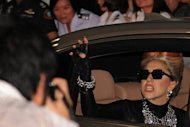 Pop diva Lady Gaga waves to fans as she leaves the airport following her arrival in Bangkok on May 23. Police in Indonesia, after refusing a permit for Lady Gaga to perform in Jakarta, say they are considering an offer from her local promoters to tone down the pop superstar's racy show