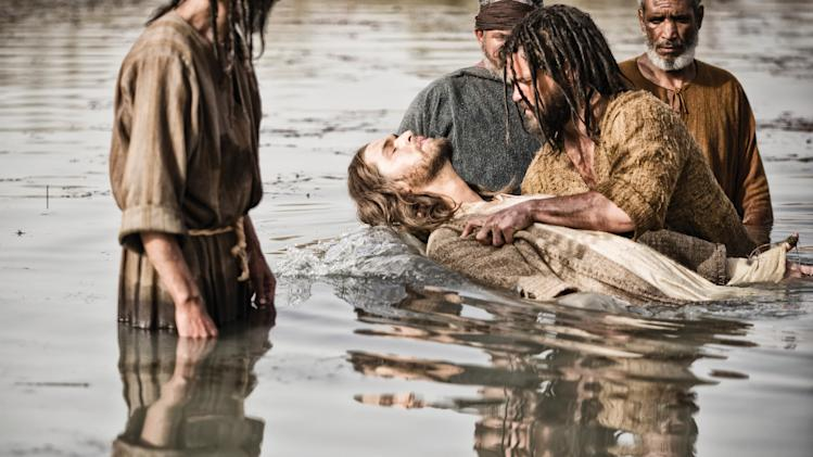 "This publicity image released by History shows Diogo Morcaldo as Jesus, center, being baptized by Daniel Percival, as John, in a scene from ""The Bible."" The History network's first installment of the miniseries ""The Bible"" was seen by 13.1 million people Sunday, March 3. The series, produced by the husband-and-wife team of Mark Burnett and Roma Downey, will air in four more installments concluding March 31, Easter Sunday. (AP Photo/History, Joe Alblas)"