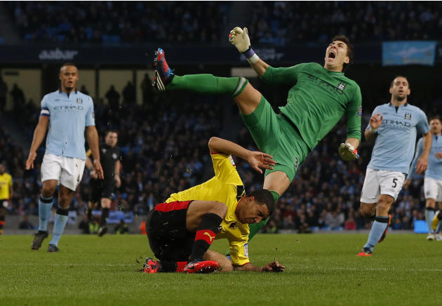 Manchester City's goalkeeper Costel Pantilimon is fouled by Watford's Troy Deeney during their FA Cup soccer match at The Etihad Stadium in Manchester