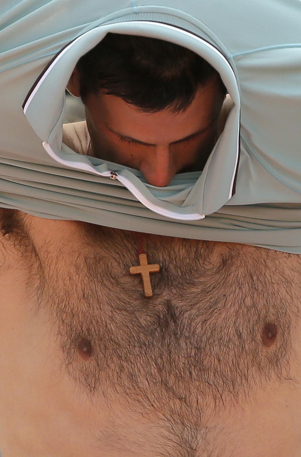 Serbia's Novak Djokovic changes his jersey during a break as he plays Germany's Tommy Haas during their quarterfinal match of the French Open tennis tournament at the Roland Garros stadium Wednesday, June 5, 2013 in Paris. Djokovic won 6-3, 7-6, 7-5. (AP Photo/Michel Spingler)