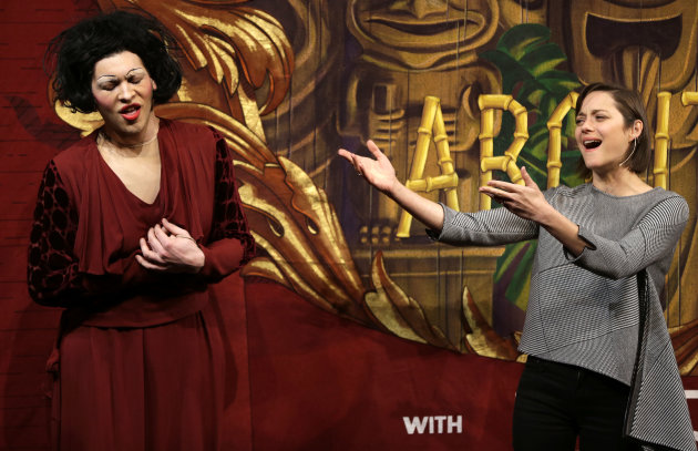 Actress Marion Cotillard, of France, right, sings Je Ne Regrette Rien, as Harvard University theatrical student Ethan Hardy, left, plays the role of Edith Piaf, in a spoof during Hasty Pudding Theatri