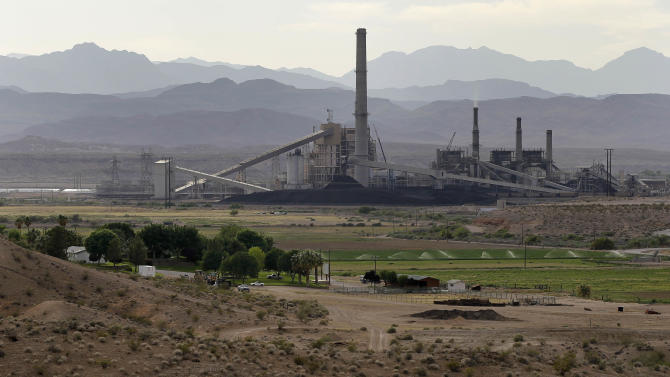 In this Monday, May 14, 2012, photo, the Reid-Gardner power station is seen near a farm on the Moapa Indian Reservation, in Moapa, Nev. Across the country, a disproportionate number of power plants operate near Indian tribal lands. Some tribes embrace the plants, which provide jobs and tax dollars to their communities. But a small group have begun to protest the plants in recent years, asking that they be closed down. (AP Photo/Julie Jacobson)