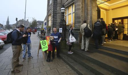 Voters wait for the polling station to open to cast their vote in Portobello near Edinburgh, Scotland