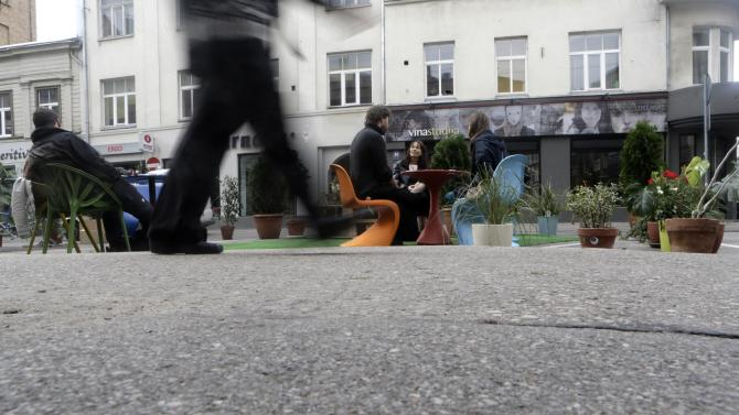 A man walks past people participating in a PARK(ing) Day event in Riga