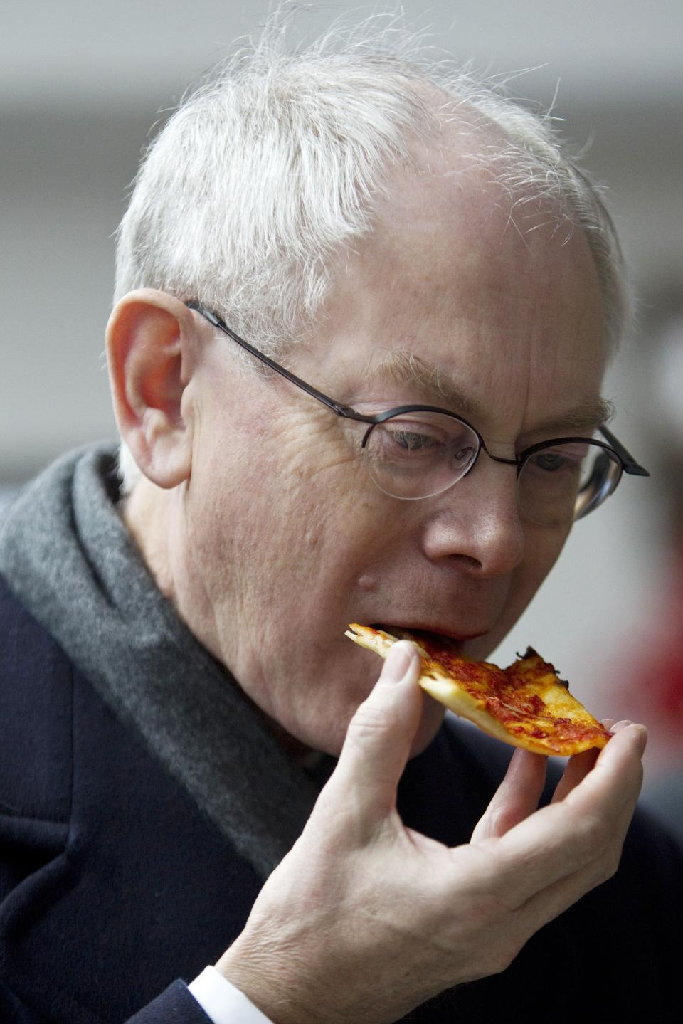 EU President Herman Van Rompuy tastes a slice of pizza during his visit at an EU-funded psychiatric clinic in Beijing Tuesday, Feb. 14, 2012. (AP Photo/Alexander F. Yuan)