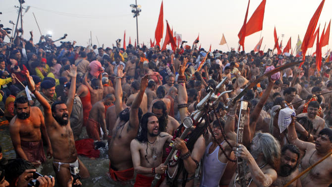 """Indian holy men shout slogans and take a holy dip at """"Sangam,"""" the confluence of Hindu holy rivers Ganges, Yamuna and the mythical Saraswati, during the Maha Kumbh festival at Allahabad, India, Sunday, Feb. 10, 2013. Millions of devout Hindus and thousands of Hindu holy men are expected to take a dip at Sangam on Sunday, the most auspicious day according to the alignment of stars, for the entire duration of Maha Kumbh festival, which lasts for 55 days. . (AP Photo /Rajesh Kumar Singh)"""