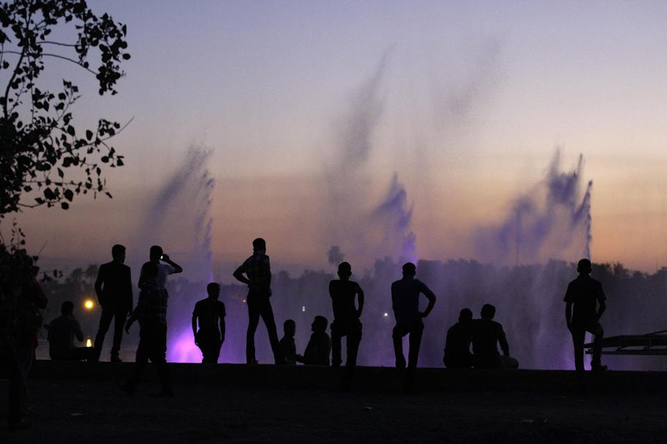 People enjoy illuminated fountains during Eid al-Adha celebrations as the sun sets on the horizon of Baghdad, Iraq, Sunday, Oct. 28, 2012. Eid al-Adha is a religious festival celebrated by Muslims worldwide. (AP Photo/Khalid Mohammed)