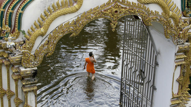 A Thai Buddhist monk talks on a cellphone while wading through floodwaters at Amarakire temple in Bangkok, Thailand, Saturday, Oct. 29, 2011. The complex network of flood defenses erected to shield Thailand's capital from the country's worst floods in nearly 60 years was put to the test Saturday as coastal high tides hit their peak. (AP Photo/Sakchai Lalit)