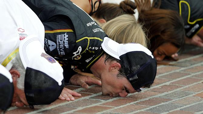 Jeff Gordon celebrates by kissing the bricks after winning the NASCAR Brickyard 400 auto race at Indianapolis Motor Speedway in Indianapolis, Sunday, July 27, 2014