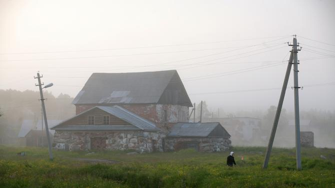 "A woman walks past a house on July 12, 2008 on the Solovetsky Islands, scene of the most notorious Soviet prison camp, later described as the ""mother of the Gulag"" by dissident author Alexander Solzhenitsyn"