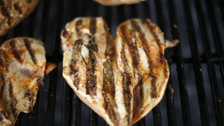 Pieces of chicken are seen on a grill at The Outdoor Grill in Culver City, Los Angeles