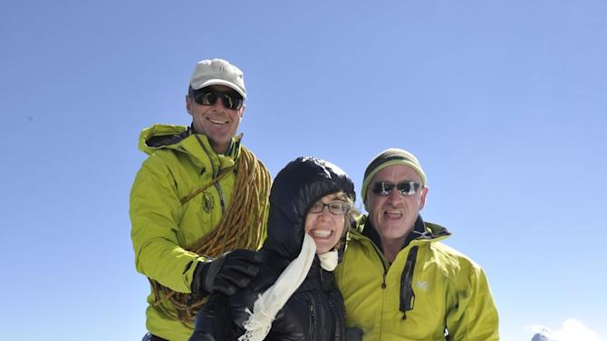 Former U.S. congresswoman Gabrielle Giffords, center, who is recovering from injuries in a mass shooting last year, and her astronaut husband Mark Kelly, right, accompanied by mountain guide Vincent Lameyre, left, stand on a ridge of the Aiguille du Midi, above Chamonix, France in the French Alps on Monday, after riding a cable car up and walking a few meters onto the snow, away from a viewing post. The outing was part of her first trip abroad since being shot in the head in a mass shooting in the U.S. last year. (AP Photo/Mike Struik, CERN (European Center for Nuclear Research))